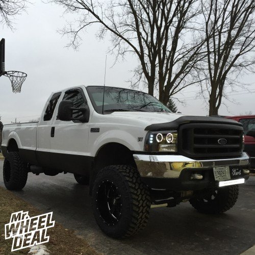 """20"""" Black Moto Metal 962 wheels with 35"""" Nitto Trail Grappler tires on a 1999 Ford F-350"""