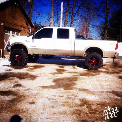 20x12 Moto Metal 969 Black and Red wheels with 37X13.50R20 Nitto Mud Grappler tires on a 2003 Ford F-250