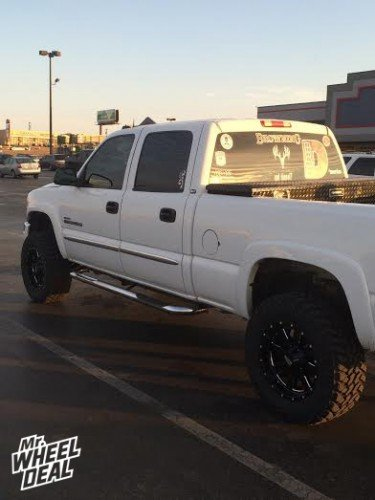 """18x9"""" Black Moto Metal 962 wheels +0 with 285/65/18 Nitto Trail Grappler MT tires on a 2003 GMC Sierra 2500"""