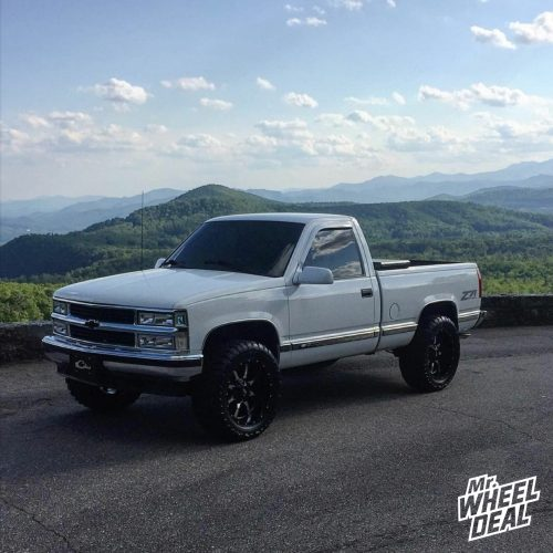 20x10 Moto Metal 970 Gloss Black Milled wheels with 33x12.50R20 Toyo Open Country MT tires on a 1996 Chevy K-1500
