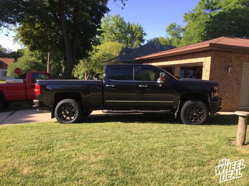 20x9 Black XD Series Buck +18mm wheels with 275/65R20 Toyo Open Country AT II tires on a 2015 Chevy Silverado 2500
