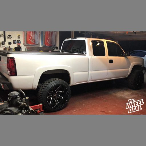 2003 Chevy Silverado 2500 with 22x14 Hostile Alpha Black Milled wheels and 33X12.50R22LT Toyo Open Country MT tires