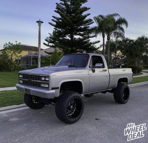 "22x14"" -75mm Black Fuel Titan wheels with LT325/50R22 AMP Mud Terrain Attack MT A tires on a 1985 Chevrolet"