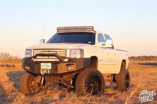 "22x12"" Hostile Sprocket Asphalt wheels with 37x13.50R22 Nitto Trail Grappler MT tires on a 2013 GMC Sierra 1500"